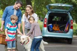 Family on summer trip with their dog